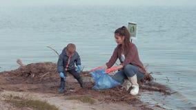 Ekologisk omsorg, mum med barnpojkevolontärer gör ren den förorenade naturen från plast- avskräde nära vatten på flodstrand lager videofilmer