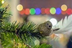 ekologiskt trä för julgarneringar En skinande guld- fågel på en filial av en julgran arkivfoto