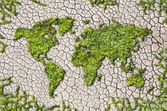 Ekologivärldskarta från gräs på sprucken jordbakgrund fotografering för bildbyråer
