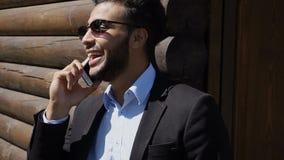 Ekonom som talar med framstickandet på telefonen som ler med skrattgropar på fa fotografering för bildbyråer
