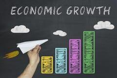 Ekonomicznego przyrosta pojęcie ręki mienia samolot jako symbol ekonomiczny podnosi kolorową biznesową mapę Fotografia Stock