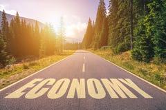 Ekonomiord som är skriftligt på vägen i bergen royaltyfri foto