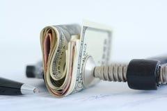 Ekonomitryckbegrepp med bunten av mynt i en kramp Royaltyfria Foton
