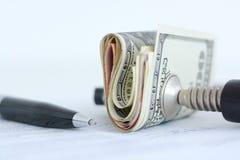 Ekonomitryckbegrepp med bunten av mynt i en kramp Arkivbilder