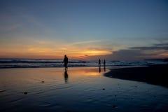 Ekostrand på solnedgången Kontur av personer som går vid waten fotografering för bildbyråer