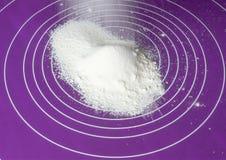 Ekranizować pszeniczną mąkę gdy tło na purpurowej krzem macie, boczny widok Obrazy Stock