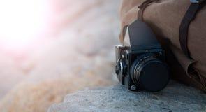 Ekranowa średnia format kamera kłama na kamieniach przeciw tłu brezentowy rocznika plecak W słońcu Zdjęcia Royalty Free