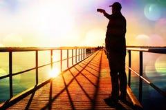 Ekranowa adra Mężczyzna na molo fotografii ranku morzu Turysta z mądrze telefonem w ręce Fantastyczny ranek z gładkim poziomem wo Zdjęcia Stock