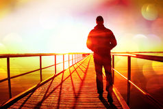 Ekranowa adra Mężczyzna sylwetki spacer na nabrzeże budowie nad morze słońce Fantastyczny ranek z jasnym niebem, gładki poziom wo zdjęcia stock