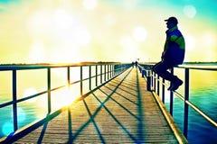 Ekranowa adra Mężczyzna w ciepłej kurtce i baseball nakrętka siedzimy na molo poręcza budowie i cieszymy się ranek przy morzem Po Fotografia Royalty Free