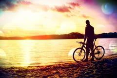 Ekranowa adra Młodego człowieka cyklisty sylwetka na niebieskiego nieba i zmierzchu tle na plaży Końcówka sezon przy jeziorem fotografia royalty free