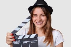 Ekranowego robić pojęcie Przyjemna przyglądająca radosna kobieta jest ubranym kapelusz, szerokiego uśmiech, chwyta filmu łupek lu fotografia stock