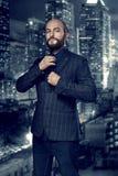 Ekranowy noir Retro stylowy moda portret zabójca lub detektyw Mężczyzna w kostiumu przystosowywa jego krawat przeciw tłu obrazy stock