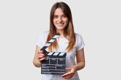Ekranowy produktywności pojęcie Piękna zadowolona uśmiechnięta młoda kobieta trzyma poruszającą clapper deskę, przygotowywa strze obrazy stock