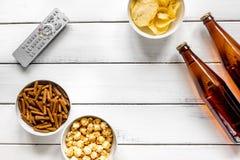 Ekranowy whatching przyjęcie z piwa, kruszek, układów scalonych i wystrzał kukurudzy tła odgórnego widoku białym drewnianym mocku Zdjęcie Stock