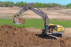 Ekskawator pracuje gdy wiadro, earthmoving maszyneria w skrzynce ekskawator kopie ziemię Zdjęcie Stock