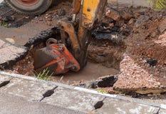Ekskawator pracuje na naprawie fajczany dostawy wody i kanalizacja na drodze Zdjęcie Stock