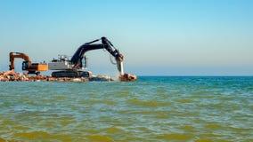 Ekskawatory rozbija beton w morze Zdjęcie Royalty Free