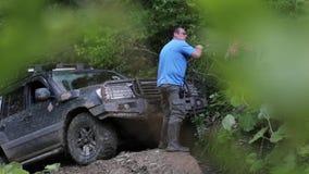 Ekspedycyjny SUV próbuje overcom niebezpiecznego powikłanego teren przy lasem przez winch zdjęcie wideo