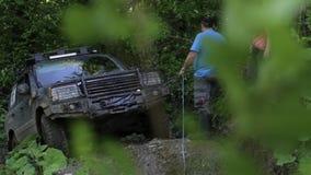 Ekspedycyjny SUV próbuje overcom niebezpiecznego powikłanego teren przy lasem przez winch zbiory