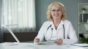 Ekspert medyczny przegląda pacjentów wyniki testu na pastylki obsiadaniu w wygodnym gabinecie zbiory wideo