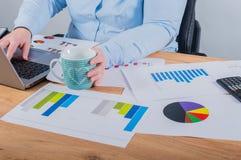 Ekspert w jej biznesie Kobieta robi niektóre notatkom w notatniku i patrzeje wykresy przy jej miejscem pracy zdjęcie stock