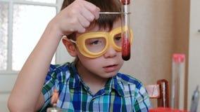 Eksperymenty na chemii w domu Chłopiec egzamininuje zawartość próbna tubka zdjęcie wideo