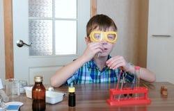 Eksperymenty na chemii w domu Chłopiec jest przyglądającym tubką upewniał się je ` s czysty fotografia royalty free