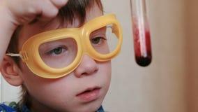 Eksperymenty na chemii w domu Zbliżenie chłopiec ` s twarz egzamininuje zawartość próbna tubka zdjęcie wideo