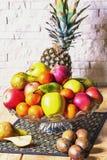 Ekspozycja świeże owoc ananas, jabłko, kiwi, mandarynka, bonkreta na drewnianym stole i biel ściany z cegieł tło, zieleni i czerw zdjęcie stock
