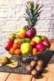 Ekspozycja świeże owoc ananas, jabłko, kiwi, mandarynka, bonkreta na drewnianym stole i biel ściany z cegieł tło, zieleni i czerw zdjęcia stock
