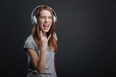 Ekspresyjna komicznie dziewczyna kołysa nowych hełmofony Fotografia Stock