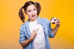 Ekspresyjna młoda dziewczyna poiting przy pączkiem trzyma w rękach zdjęcie royalty free