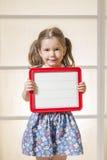 Ekspresyjna mała dziewczynka trzyma pustą magnesową deskę Obraz Royalty Free