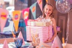 Ekspresyjny dziecko śmia się podczas gdy trzymający dużych prezenty urodzinowych zdjęcia royalty free