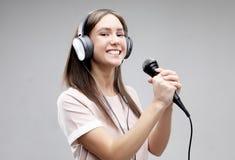 Ekspresyjny dziewczyna śpiew z mikrofonem i hełmofonami fotografia stock