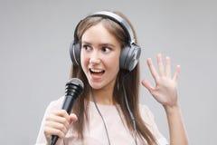 Ekspresyjny dziewczyna ?piew z mikrofonem i he?mofonami obrazy royalty free