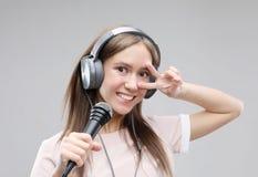 Ekspresyjny dziewczyna ?piew z mikrofonem i he?mofonami zdjęcia stock
