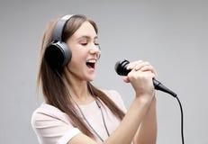 Ekspresyjny dziewczyna ?piew z mikrofonem i he?mofonami zdjęcie stock