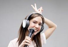 Ekspresyjny dziewczyna ?piew z mikrofonem i he?mofonami fotografia stock