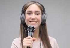 Ekspresyjny dziewczyna ?piew z mikrofonem i he?mofonami zdjęcia royalty free