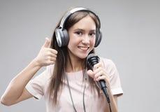 Ekspresyjny dziewczyna ?piew z mikrofonem i he?mofonami obraz stock