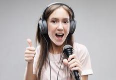 Ekspresyjny dziewczyna ?piew z mikrofonem i he?mofonami zdjęcie royalty free