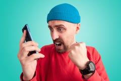 Ekspresyjny facet martwi się podczas gdy oglądający na ekranie smartphone fotografia royalty free