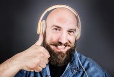 Ekspresyjny mężczyzna słucha muzykę z hełmofonem fotografia stock