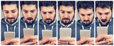Ekspresyjny młody człowiek używa smartphone fotografia stock