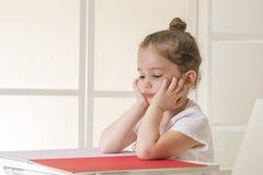 Ekspresyjny małej dziewczynki obsiadanie przy biurka czekaniem fotografia stock