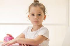 Ekspresyjny małej dziewczynki obsiadanie przy biurka czekaniem Zdjęcia Royalty Free