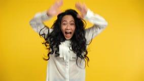 Ekstatische asiatische Frau, die mit Freude und den Armen herauf das Feiern des Erfolgs springt stock footage