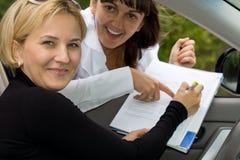 Ekstatische Frau, die für ihren Neuwagen unterzeichnet Lizenzfreies Stockfoto